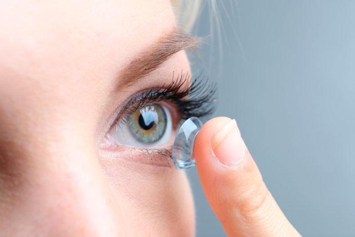 надевает контактные линзы